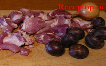 на разделочной доске лежит свинина порезанная  порционными кусками для жарки, семь больших свежих слив и одна луковица