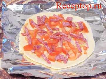 на фото основа для пиццы с луком и помидорами и колбасой