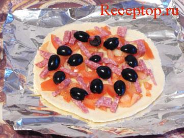 на фото основа для пиццы с луком и помидорами, колбасой и маслины