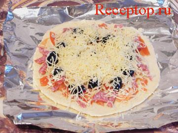 на фото основа для пиццы с луком и помидорами, колбасой и маслины посыпаны сыром