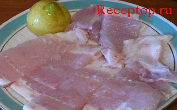 на блюде филе морского языка нарезанное на куски, половинка лимона