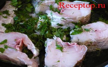 на фото рыба лежит на сковороде, воды добавим до половины куска рыбы, лук, зелень петрушки, укроп
