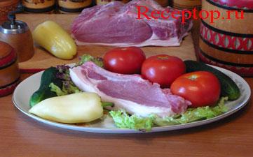 на блюде лежит порционный кусок свиной корейки с косточкой, один сладкий перец, три свежих помидора и два свежих огурца, листья салата, рядом на разделочной доске большой кусок свиной корейки с ребрами, сладкий перец, ручная мельница для черного перца