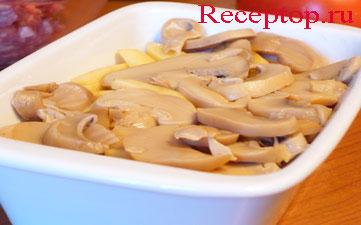 на фото маринованные или соленые грибы сверху картофеля, который уложен поверх мясного фарша в жаропрочной форме