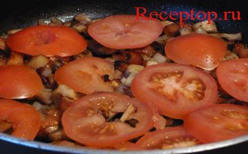 на фото помидоры нарезанные кружками, положили на  обжаренные грибы шампиньоны