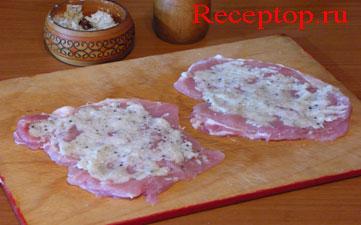 фото на двух отбитых порционных кусках свиной корейки без косточки намазана смесь протертого сала с чесноком
