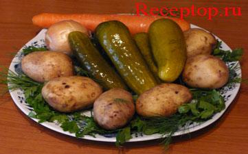 на блюде лежит пять соленых огурцов, шесть картофелин, одна мороковь, одна головка лука и укроп с петрушкой